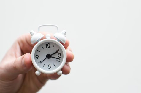 a hand hold a small clock